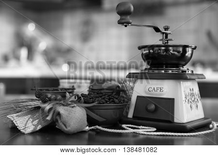 Grinder with coffee beans in copper bowls and Cup with composition of jute