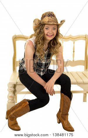 a cowgirl with down syndrome sitting on a bench with a big smile.