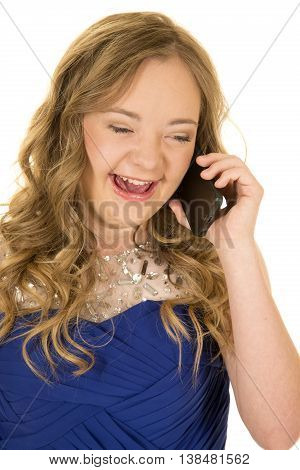 a woman with down syndrome talking on her phone with a big smile on her face.