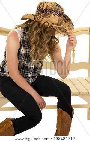a cowgirl with down syndrome sitting on a bench holding on to her western hat.