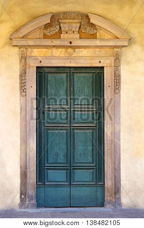 a cross decorates the door painted green and very consumanta of an ancient church