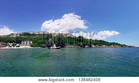 Summer vacation background with a hotel on the seashore and a boat floating on the water. Panoramic view of the coast of Black Sea Balchik city Bulgaria