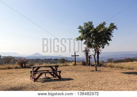 Wood Picnic Table And Seats On Hilltop In Dry Landscape