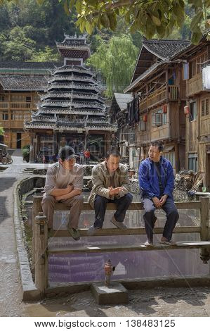 Zhaoxing Dong Village Guizhou Province China - April 8 2010: Three Asians rest sitting on bench near fire pond opposite drum tower and wooden huts Village of ethnic minorities morning spring.