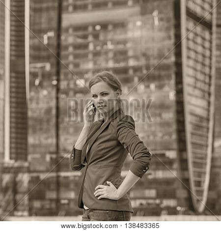 Beautiful young blonde in a blue jacket calling by phone