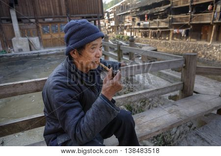 Zhaoxing Village Guizhou China - April 8 2010: Elderly Asian man in blue dress sitting on bench in middle of countryside of wooden houses of ethnic minorities with bamboo smoking pipe in hand.
