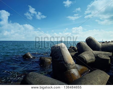 Huge stones in the sea water near the harbor at Balchik city Bulgaria. Summer vacation background with a ship floating on far.