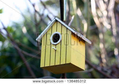 Little yellow bird house in the garden