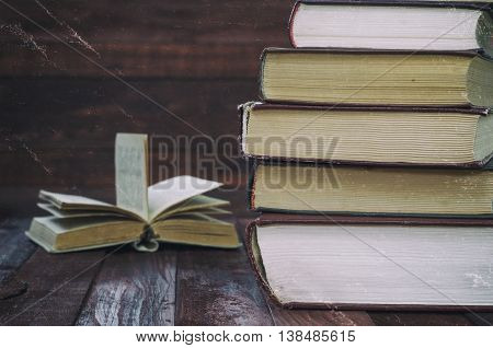 stack of book on a brown wooden table in the background an open book