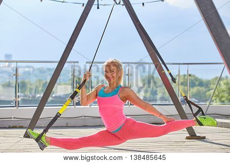 Kiev, Ukraine - May 12, 2016: TRX training on the roof of sport centre in colorful suits in sunny day