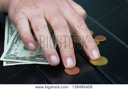 Hand with dollars and coins on black table
