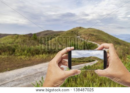 Hand male asian holding Smartphone taking picture of Mountain hill viewpoint scenic landmark at Ban I-Tong Pilok Thong Pha Phum. Kanchanaburi Thailand. beautiful scenery for background