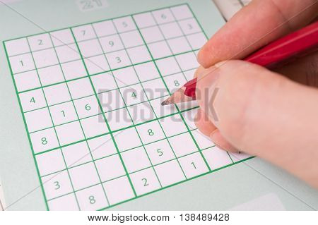 Sudoku Crossword And Hand Holding Pencil Is Solving Puzzle.