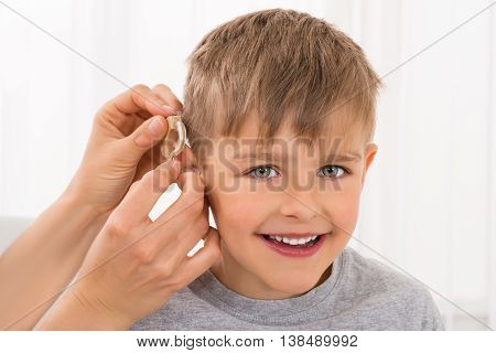 Close-up Of A Doctor Fitting Hearing Aid On Smiling Boy's Ear