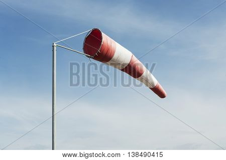 Red and white windsock wind filled blue sky background.