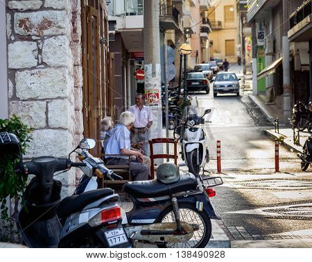 SITIA, CRETE, GREECE - JUNE 28, 2016: Old man sit on chairs at the street and talk about life in Sitia town