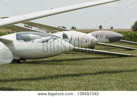gliders at green airfield with blue sky