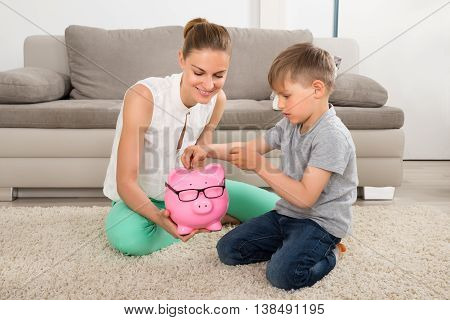 Happy Mother Looking At Boy Inserting Coin In Piggybank