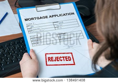 Business woman is holding mortgage application with rejected stamp.