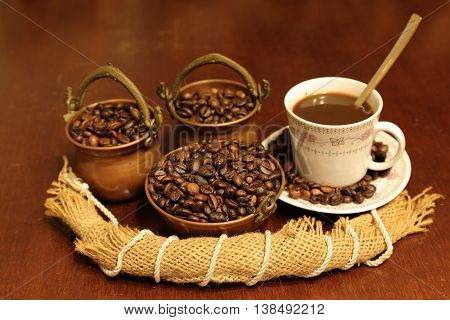 Coffee seeds in copper bowls cups and liquid composition of jute