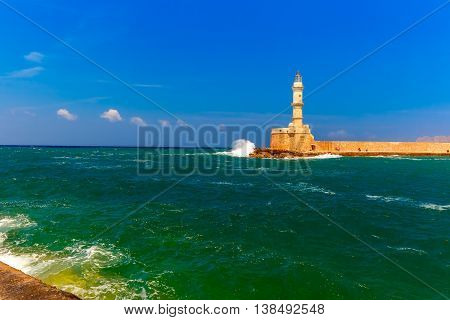 Waves beat against the lighthouse in old harbour of Chania in the summer sunny day, Crete, Greece