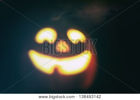 Vintage filtered defocused image of a smiling halloween jack o lantern pumpkin