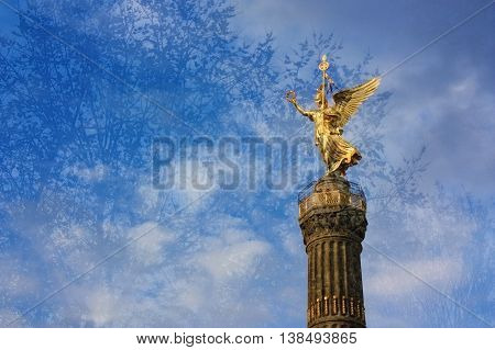 The Victory Column Golden Elsa in Berlin Germany. Picture taken threough the glass of the bus with the reflections of the trees.