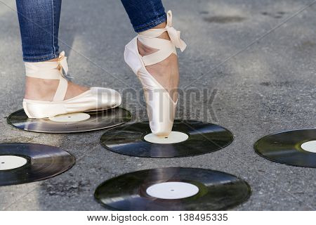 Feet girl in Ballet shoes stand amid vinyl discs that lie on the road.