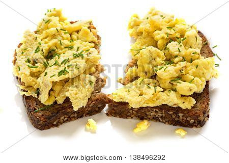 fresh scrambled eggs on a slice of rustic of wholemeal bread in two halves isolated with shadows on a white background selected focus and very narrow depth of field