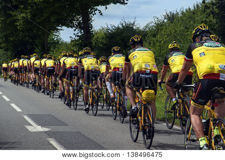 Schlagsuelsdorf Gemany - July 10 2016: large group of sporting bikers in yellow shirts at the bicycle race Grand Prix of Lübeck on the highway from Rieps to Ratzeburg in Northern Germany