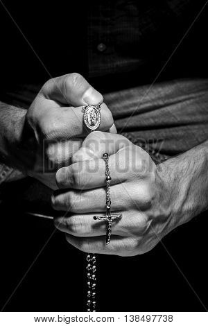 Praying Hands with rosay in black background