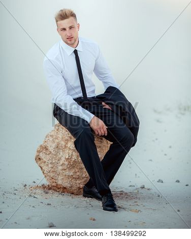 Portrait of young businessman in sand quarry. Blonde hair
