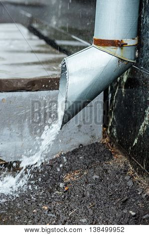 rainwater flow from the drainpipe installed on brick wall. Protection ftom heavy rains.