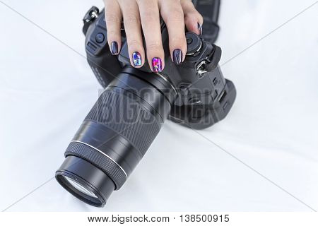 single-lens reflex camera in the hands of a girl with a beautiful manicure on white background