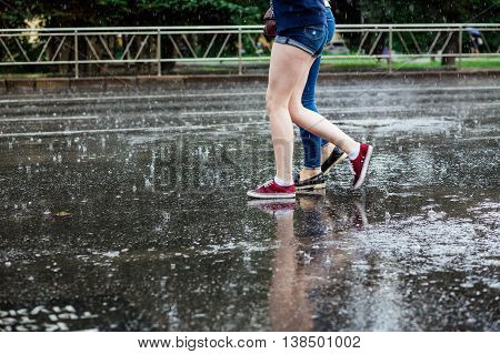 Two young women in boots crossing the street legs during heavy rain.