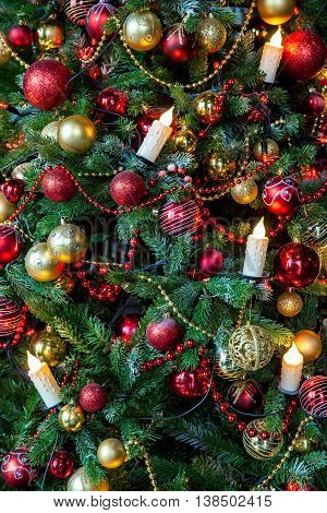 Christmas background. Green Classic New Year tree decorated with christmas balls and candles