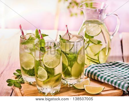 Country drink. On wooden boards are glass jug with transparent cocktail and lime . A drink number hundred sixty two with ice cubes . Country life. Light background.