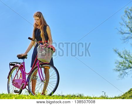 Bikes bicycle girl. Girl wearing polka dots dress looking down keeps bicycle with flowers basket. Girls aganist blue sky.