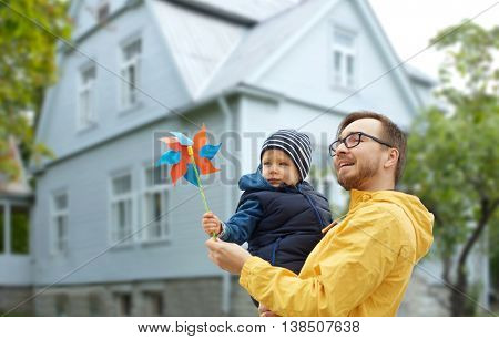 family, childhood, fatherhood, leisure and people concept - happy father and little son with pinwheel toy outdoors over living house background