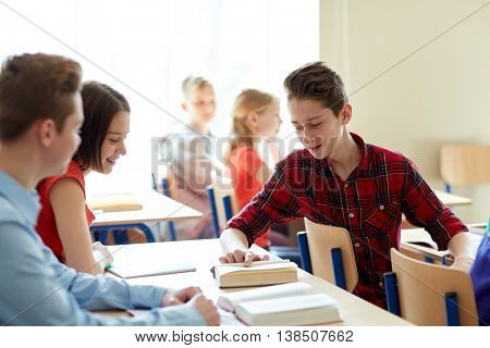 education, learning and people concept - group of students discussing book at school lesson