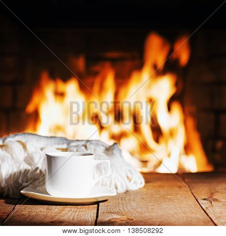 White Cup Of Tea Or Coffee And Woolen Scarf Near Fireplace.