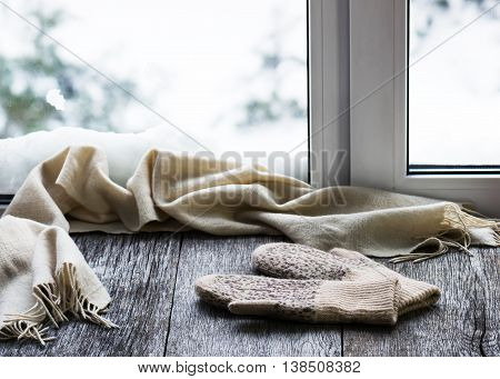 Beige Woolen Scarf And Mittens Located On Wooden Window Sill.