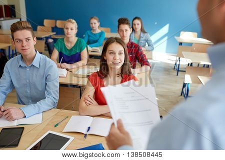 education, school, teaching, learning and people concept - group of happy students and teacher with papers or tests
