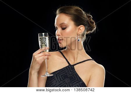 holidays, nightlife, drinks, people and luxury concept - beautiful young asian woman drinking champagne at party over black background and spotlights