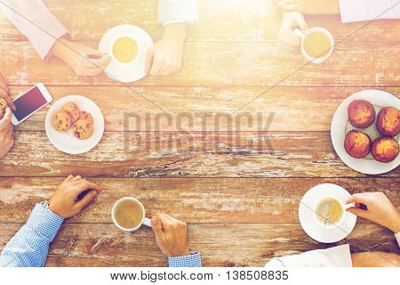 business, people and team work concept - close up of creative team meeting and drinking coffee during lunch in office