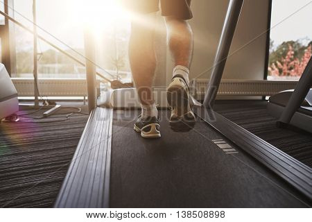 sport, fitness, lifestyle, technology and people concept - close up of man legs walking on treadmill in gym from back