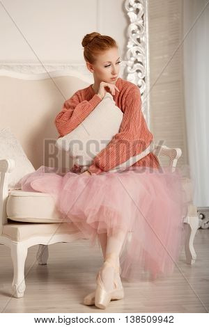 Pretty young ballerina grieves. Girl hugging pillow. Ballerina in tutu and pink sweater.