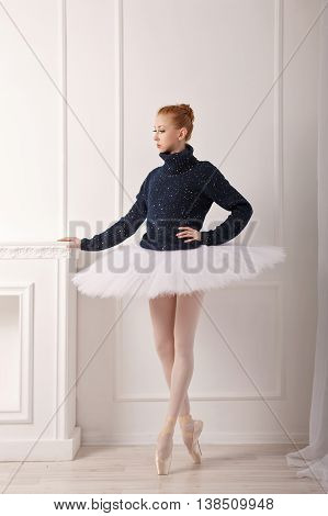 Pretty young dancer standing by the fireplace. A girl wearing a tutu and a black sweater.