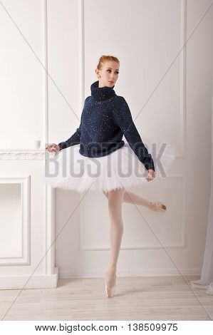 Pretty young ballerina standing by the fireplace. A girl wearing a tutu and black sweater.