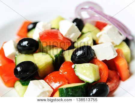 Greek salad closeup. The mixture of the vegetables: pepper cucumber onion olives and cheese.